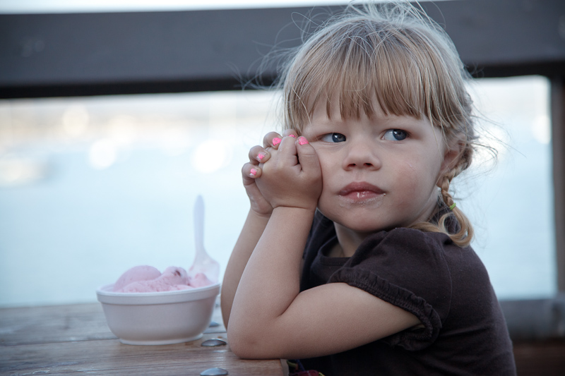 Charlotte eating ice cream with a thoughtful gaze while at Stearns Wharf in Santa Barbara.