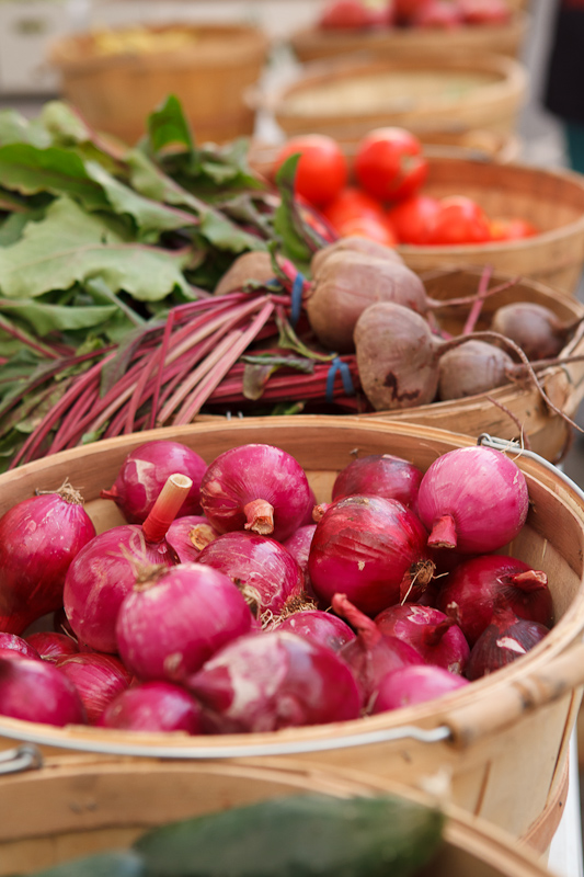 Red onions and beets in bushel baskets at the Provo Fresh Wednesday Farmer's Market in Downtown Provo